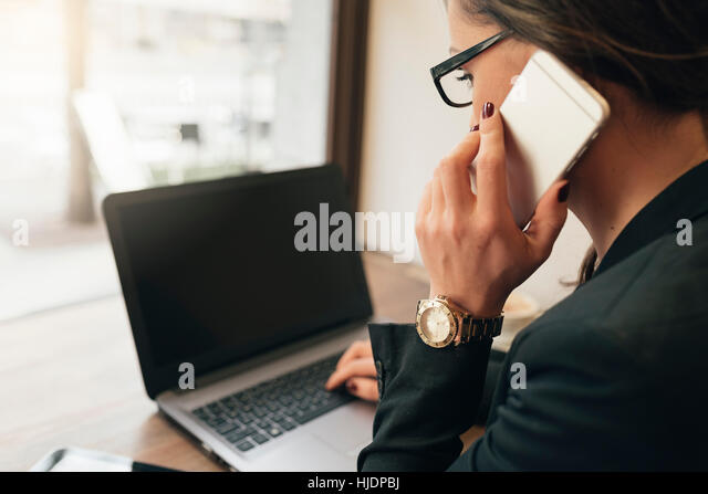 Businesswoman using his laptop and mobile in the Coffee Shop. Business Concept - Stock Image
