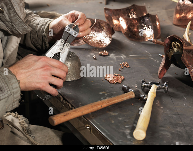 Cropped image of blacksmiths hands working with copper rivets - Stock Image
