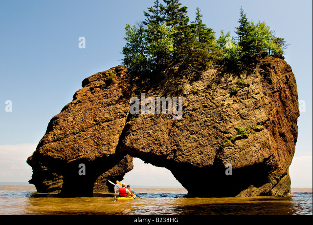 Canada New Brunswick Kayakers paddling through Hopewell Rocks at high tide Bay of Fundy Flower Pot Rocks - Stock Image