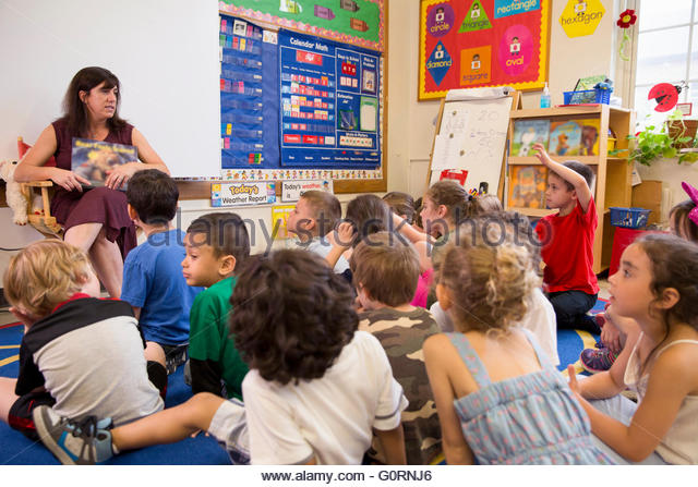 Teacher reading story to young students in classroom - Stock Image