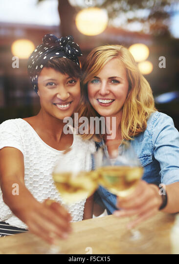 Fun attractive young female friends celebrating with white wine clinking their glasses in a toast as they smile - Stock Image
