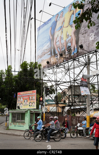 Motorcycles driving past advertising billboards. Cebu City, Cebu, Visayas, Philippines. - Stock Image