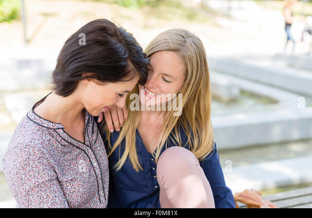 Two girlfriends laugh together and talk - Stock Image