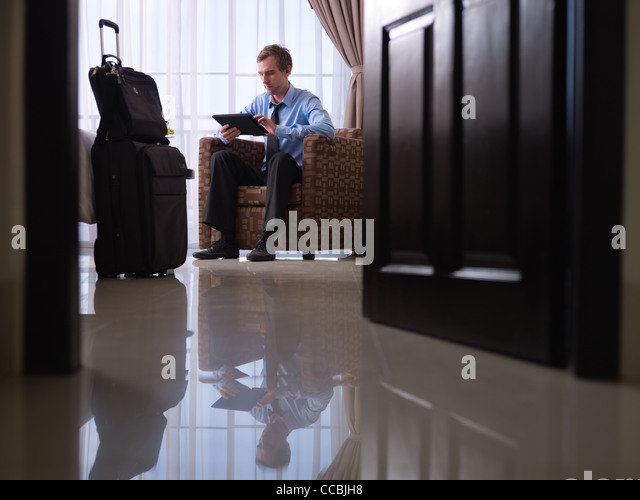 Mid adult caucasian manager typing on tablet pc in hotel room during business travel. Low angle view, full length - Stock Image
