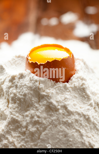 Opened Egg Shell with Yolk on Flour - Stock Image