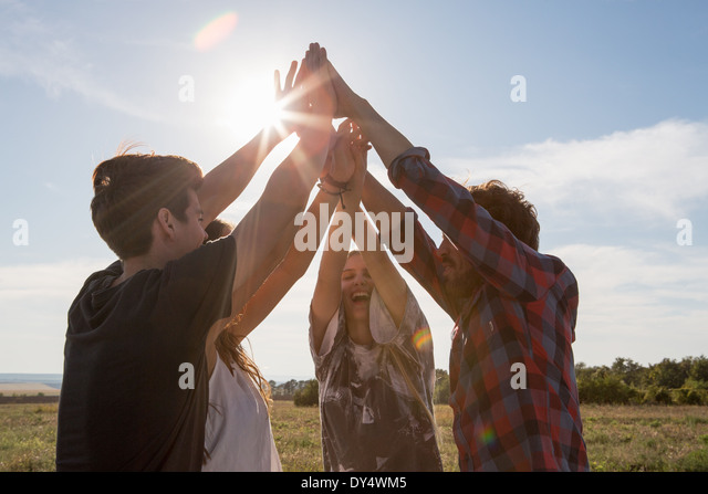 Four friends holding hands with arms raised - Stock Image