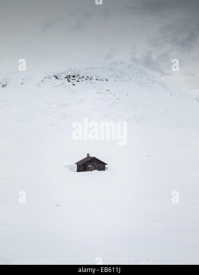 mountain hut in winter landscape with mountain top behind - Stock Image