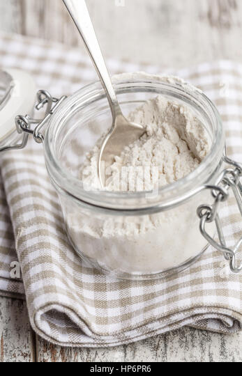 white flour in a glass jar - Stock Image
