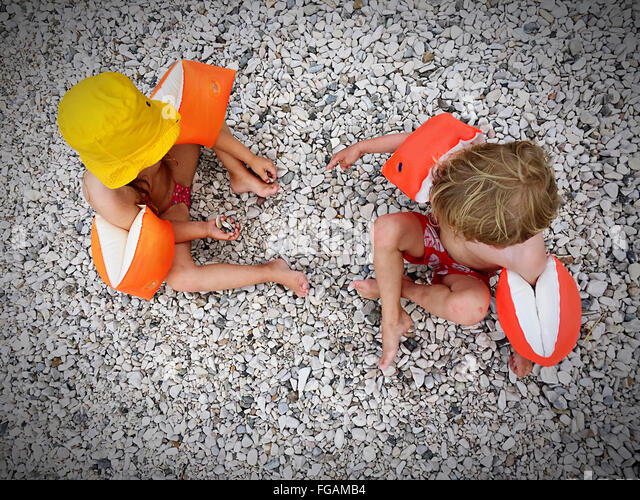 Directly Above Shot Of Children Wearing Water Wings Sitting On Pebbles - Stock Image