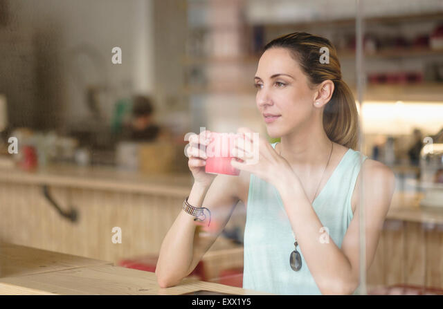 Woman holding coffee cup in cafe - Stock-Bilder