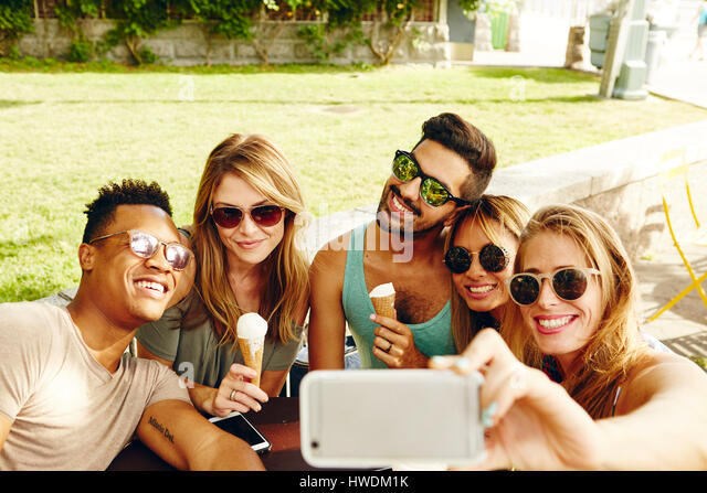 Male and female friends taking smartphone selfie in park - Stock-Bilder