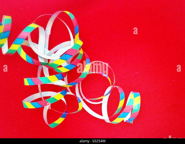 Paper streamers on red background - Stock Image