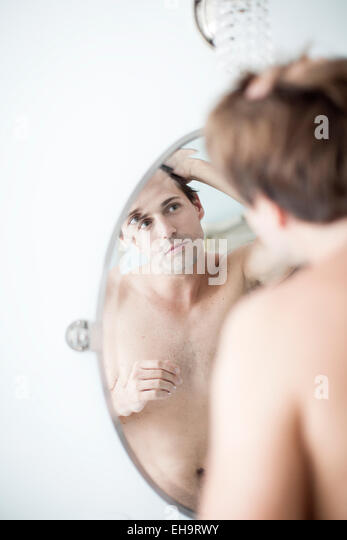 Man examining hairline in mirror - Stock Image