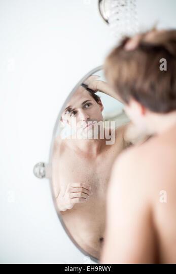 Man examining hairline in mirror - Stock-Bilder