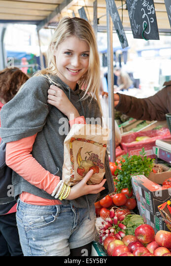 Young woman at greengrocer's buying fresh fruits and vegetables - Stock Image