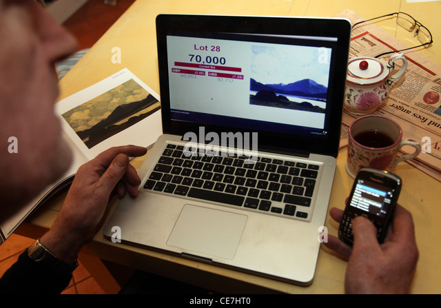 bidding online at a Whyte's fine art auction - Stock Image