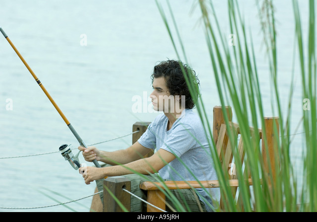 Young man fishing on dock - Stock Image