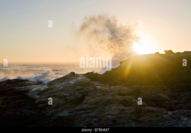 A large wave crashes over rocks along the California Coast at sunset. - Stock Image