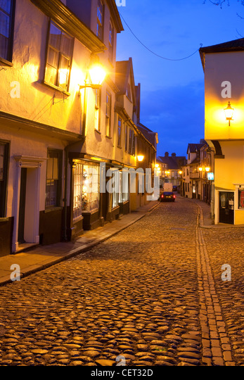 Elm Hill, an historic cobbled lane featuring many buildings from the Tudor period, illuminated at dusk. - Stock Image