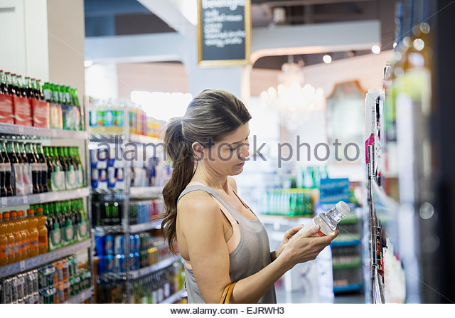 Woman reading label on bottle in grocery store - Stock Image