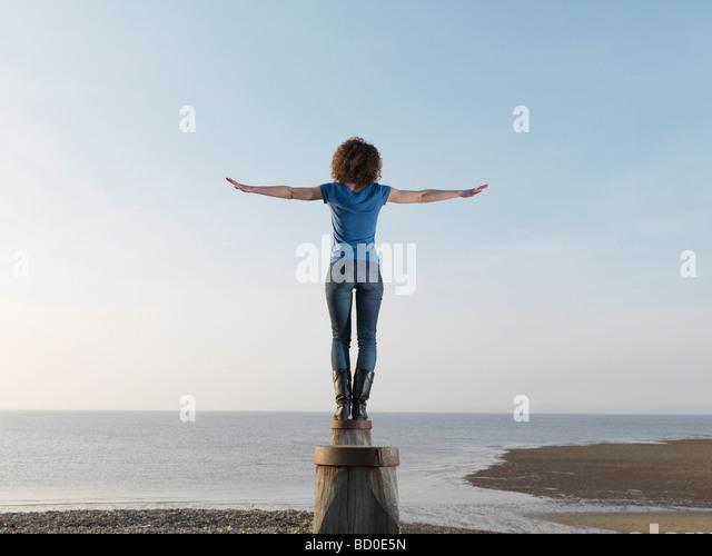 Woman balancing on wooden post - Stock Image