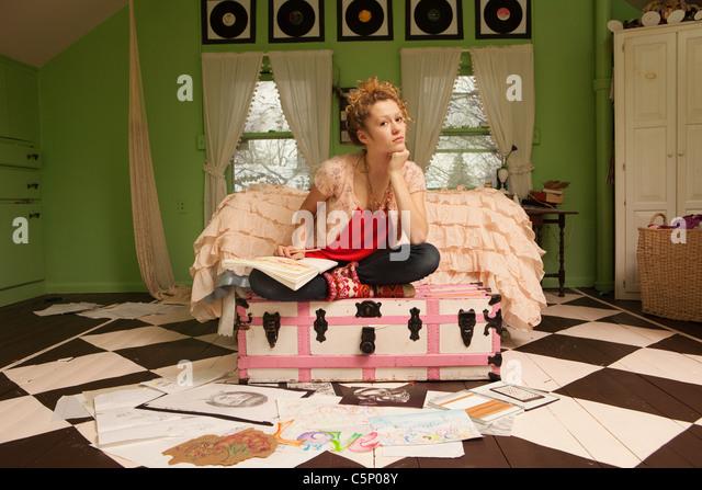 Teenage girl sitting on ottoman with drawings on bedroom floor - Stock-Bilder