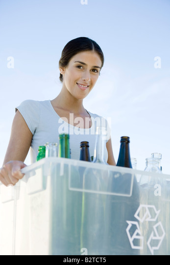 Woman carrying recycling bin filled with glass bottles, smiling at camera - Stock Image