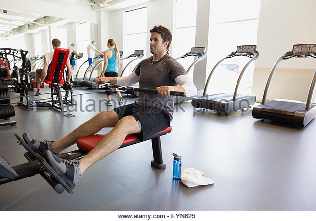 Man doing seated cable row at gym - Stock Image