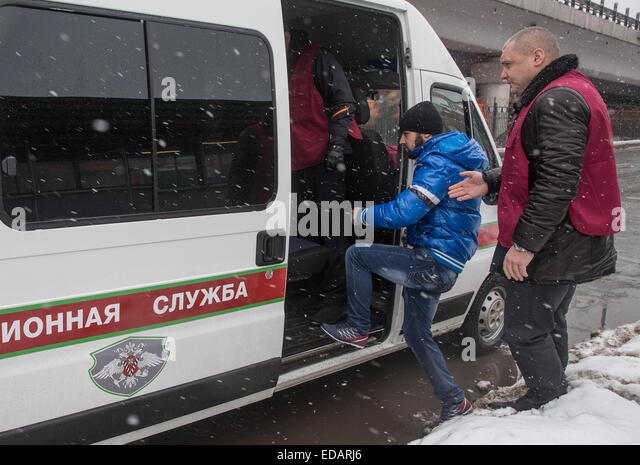 Moscow, Russia. 4th Jan, 2014. Officers of Russia's Federal Migration Service detain a man during a raid near - Stock-Bilder