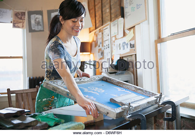 Female design professional using silk screen at workshop - Stock Image