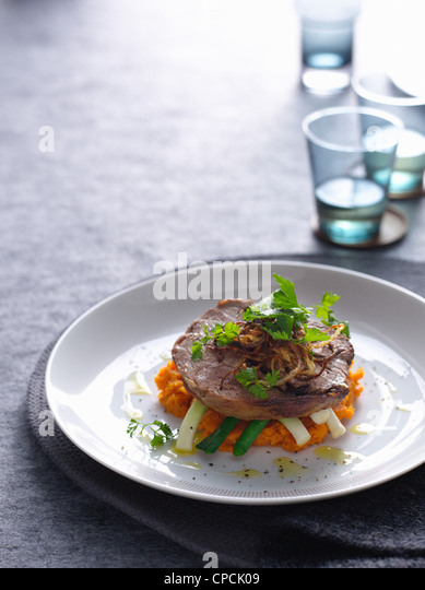 Plate of pork with vegetables - Stock Image