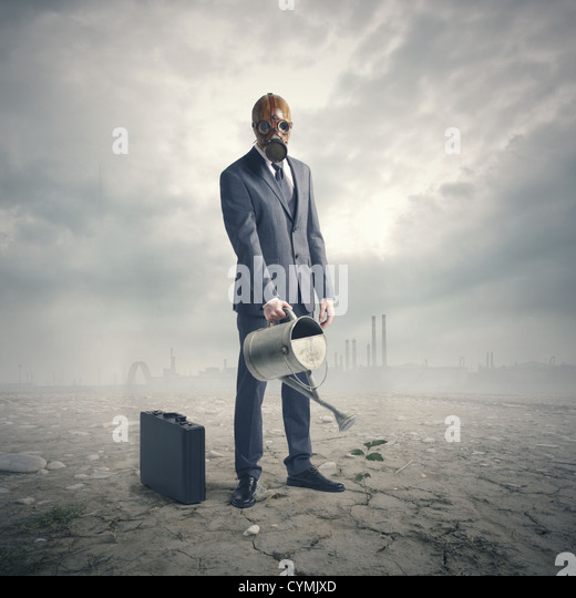 environment concept: businessman watering a lone plant in a barren desert. - Stock-Bilder