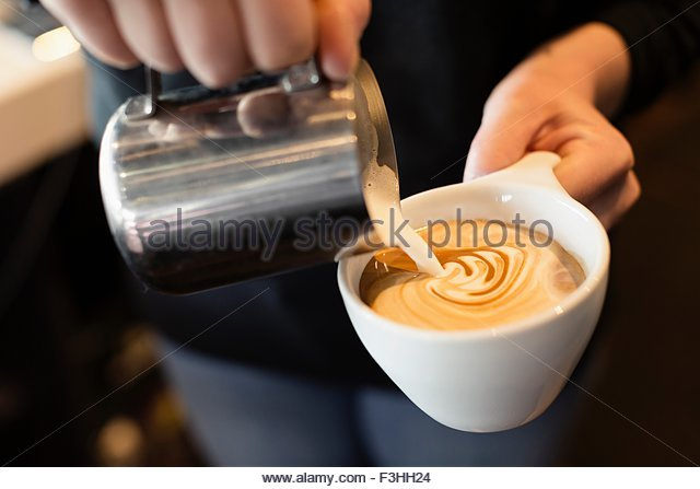 Coffee shop barista pouring milk into coffee, mid section, close-up - Stock-Bilder