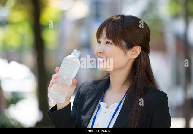 Smiling Businesswoman Holding Bottled Water - Stock Image