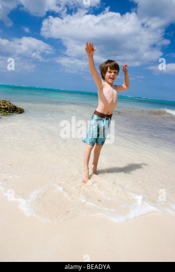 A young boy jumping on the beach, Cable Beach, Nassau, Bahamas, Caribbean - Stock-Bilder