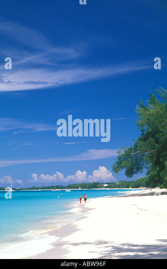 Caribbean Grand Cayman Island Seven Mile Beach couple walking in surf - Stock Image