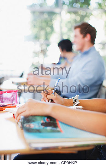18-19 years,20-24 years,arm,book,casual clothing,caucasian,classroom,college,color image,day,education,focus on - Stock Image