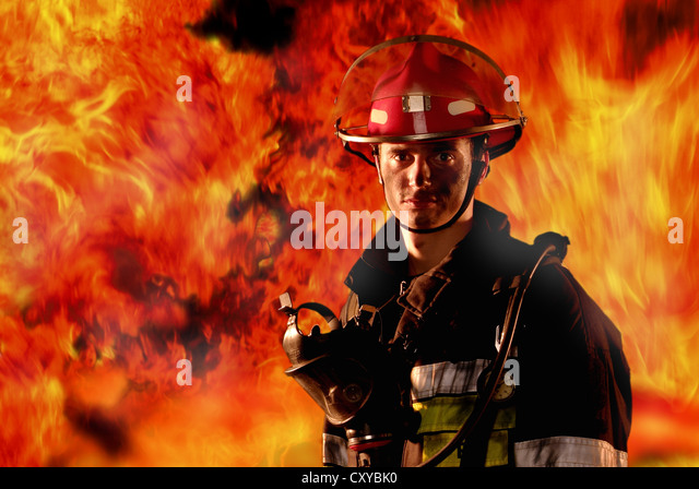 Firefighter in front of a wall of fire - Stock Image