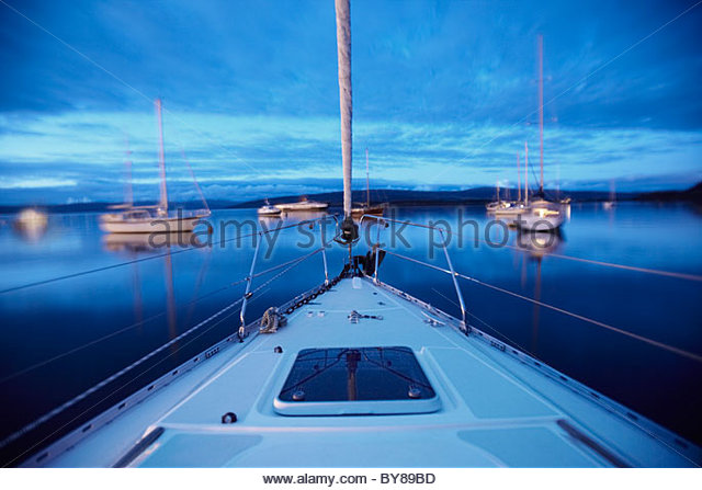 Bow of boat sailing on lake - Stock Image