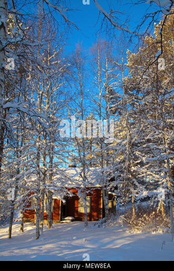 Snow covered wooden house on a sunny winter day. - Stock Image