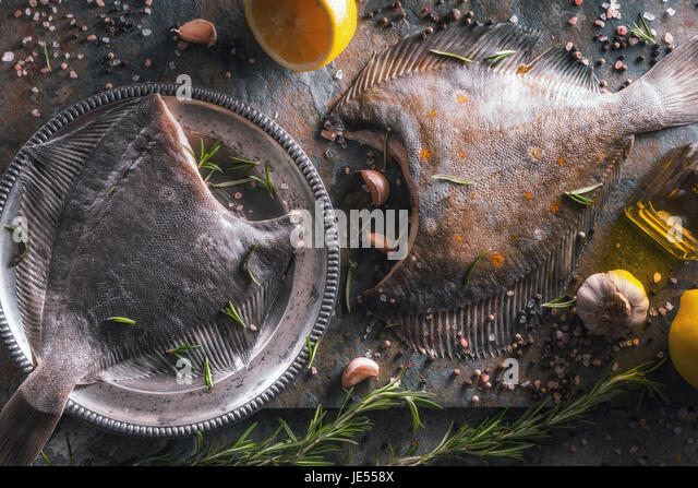 Raw flounders with different seasoning on stone horizontal - Stock Image