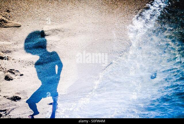 Annonimous silhouette walking on the beach, mediterranean sea, Catalonia, Europe - Stock Image