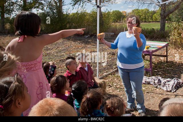 Americorps Volunteer Talks To Elementary School Children in Community Garden - Stock Image