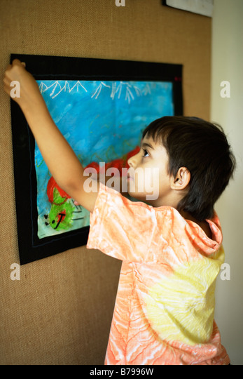 Six year old boy pins up his artwork - Stock Image
