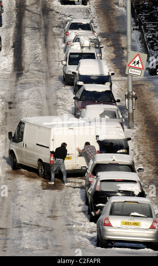 Two men push a van on a steep street in Glasgow, Scotland which is covered in ice and snow making driving and walking - Stock-Bilder