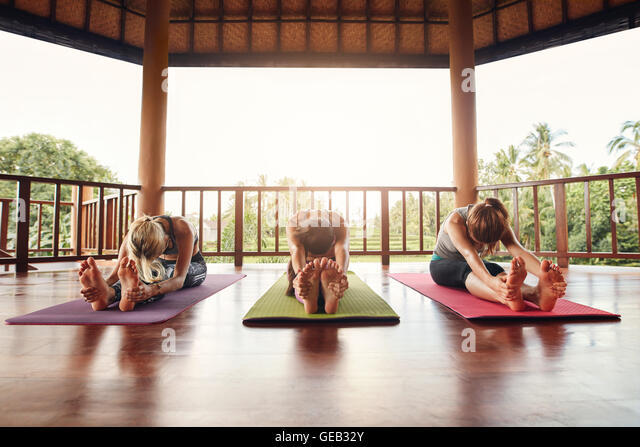 Three women doing yoga together at class, practicing paschimottanasana pose. Fitness females stretching forward - Stock Image