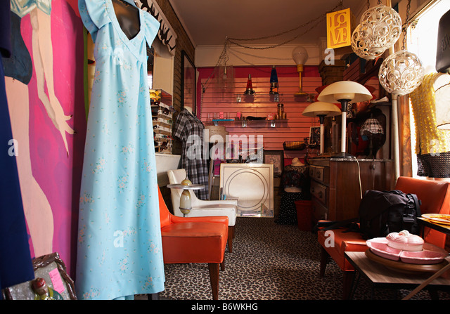 Clothing and Furniture in Crowded Second Hand Store - Stock Image