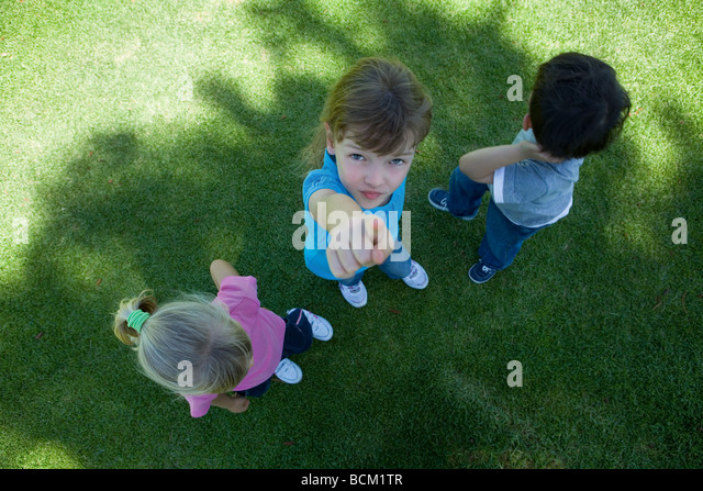 Three children standing on grass, in shade, one girl pointing at camera, view from directly above - Stock Image