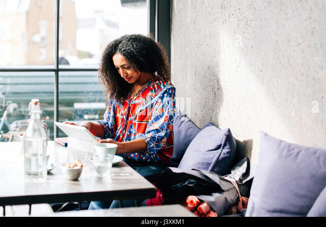 Mid adult woman using digital tablet in cafe - Stock Image