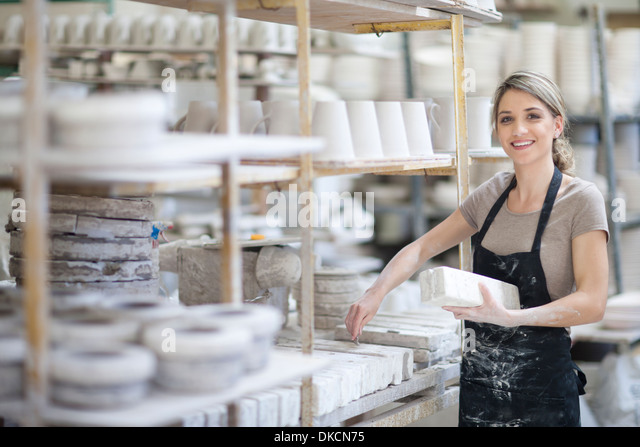 Potter arranging clay blocks onto shelf at crockery factory - Stock Image